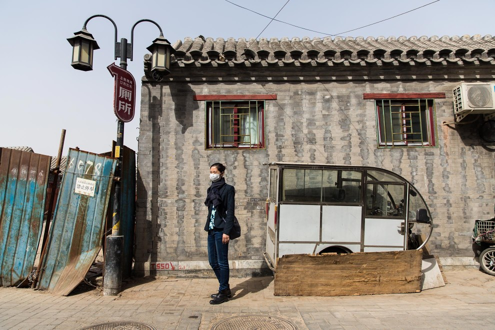"Ms. Liu (30) pauses during a walk through one of Beijing's traditional hutong neighbourhoods. ""Of course I worry about the pollution"", she says. ""I don't have a good stomach or throat, so I pay attention to the pollution. I think this issues should of been addressed year ago."" PM2.5 reading - 107 - Unhealthy for Sensitive Groups"