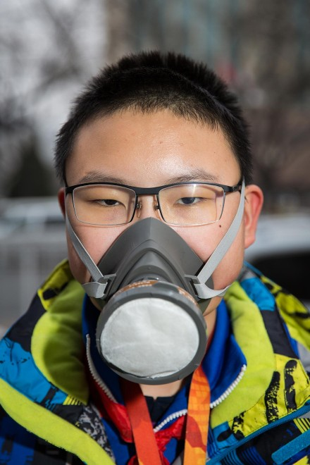 "Qi (name changed), a 13-year old middle school student, wears an advanced air filtration mask in central Beijing. ""I'm more concerned about the pollution than my parents. Since 2012, my parents told me to stay inside more. I asked my parents to buy this for me. My classmates think I'm strange."" PM2.5 reading - 188 - Unhealthy"