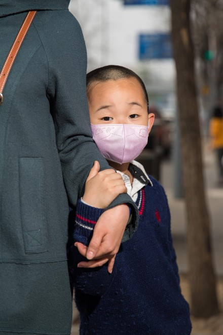A young boy stands with his mother at a bus stop in the west of Beijing. As well as the elderly, children are particularly susceptible to the adverse health effects of air pollution.Many young children can now be seen on the streets of Beijing wearing masks, in an effort by their families to protect them. PM2.5 reading - 204 - Very Unhealthy