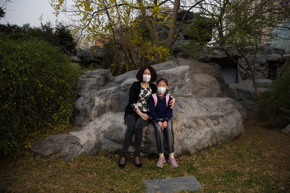 "Mrs. Liu sits with her daughter in a small garden outside of her office in the west of Beijing. ""I want to protect my daughter. She's young. She isn't able to protect herself"", she explains as to why she makes her daughter wear a mask. ""I'm sure the PM2.5 is bad for people's health. I'm thinking of sending her overseas. I think it will take a long time to clear the air. I don't want my daughter to have to live with this situation."" PM2.5 reading - 204 - Very Unhealthy"