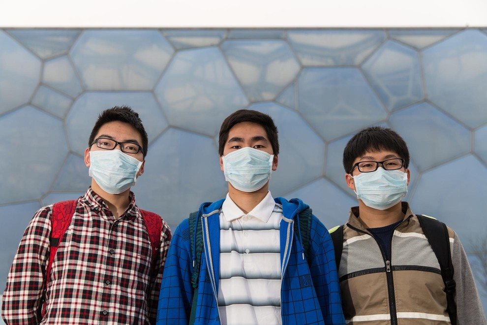 "Students Liu (21), Xu (22) and Han (21) stand near the Olympic Swimming Center during a visit to Beijing from southern China. ""We never wore a mask before. After we arrived in Beijing we bought it"", explains Liu. ""The air quality is not good"", continues Xu. ""More and more people pay attention to this. We should pay more attention to this problem. Every person has to start the change.""  PM2.5 reading - 218 - Very Unhealthy"
