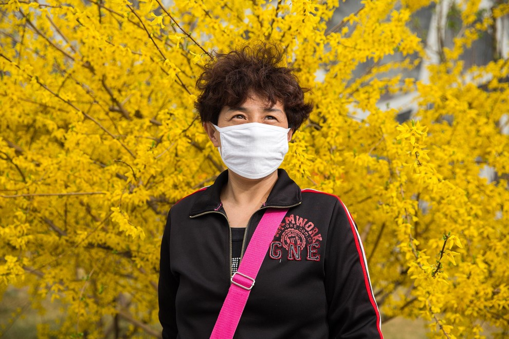 "A tourist (name withheld) from Heilongjiang province, in north-west China, visits the Olympic green in central Beijing. ""I knew from TV that the air quality is bad in Beijing, so I bought it before I came here"", she says. "" In Heilongjiang, the air is better than here but in the [city] downtown area it's similar"". PM2.5 reading - 218 - Very Unhealthy"