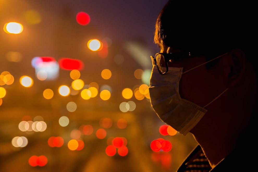 Zhao (25), an office worker, stands on a bridge above a busy highway in the centre of Beijing. PM2.5 reading - 223 - Very Unhealthy