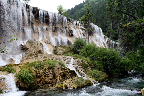 A wide waterfall cascading over rocks into the waters below in the Jiuzhaigou national park in southern China.