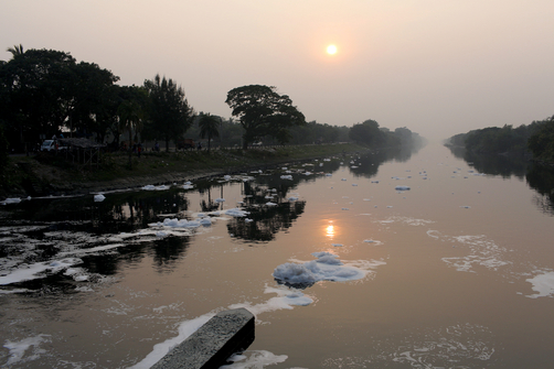 A polluted river on the outskirts of Kolkata. Nearby factories release waste water which produces foam in the water.
