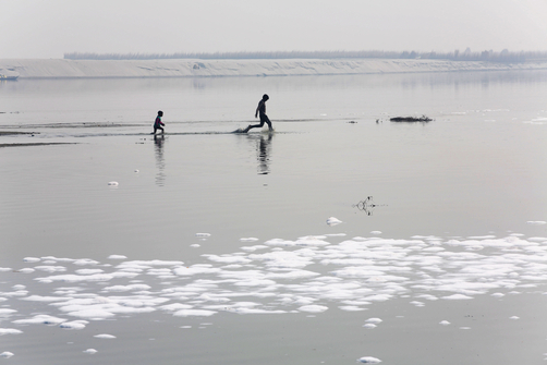 Children run through the shallows of the Ganges River near to pollution from nearby leather factories.