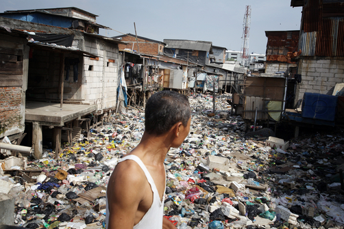 A man walks past a river that has been completely covered with refuse in a slum community in Muara Baru, in north Jakarta.