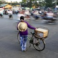 A women with a bicycle waits to cross a busy street in Ho Chi Minh City.