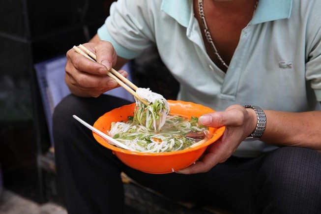 A man eating a bowl of Pho, traditional Vietnamese noodles.