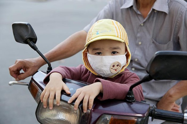 A young Vietnamese child wearing an air pollution mask.