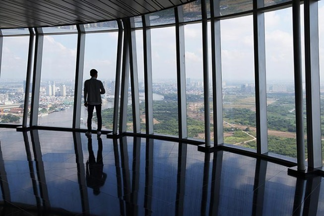 A man looks out from the viewing deck of the Bitexco Financial Tower in Ho Chi Minh City.
