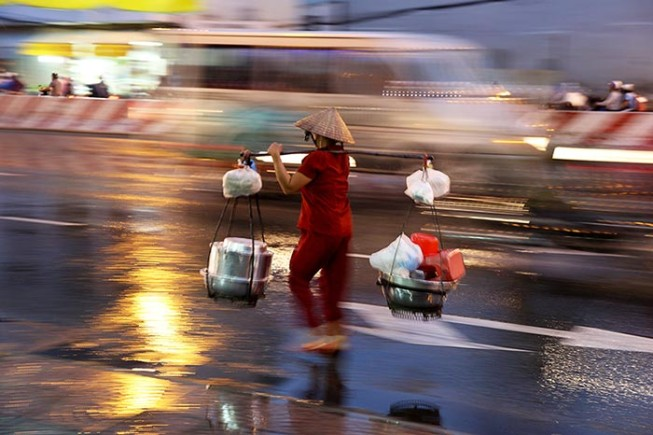 A woman carrying goods down a busy street in central Ho Chi Minh City.