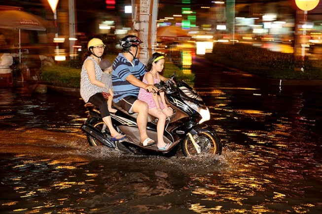 A family ride a motorbike through flooded streets after a rainstorm in Ho Chi Minh City.