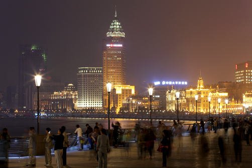 People walk along the Bund waterfront area at night.