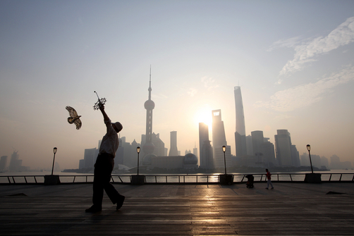A man flies a paper kite at sunrise in front of the distinctive Pudong skyline.