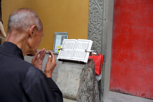 A monk prays at the Jade Buddha Temple.