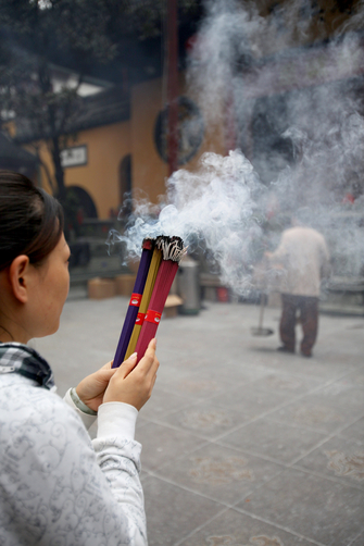 A woman prays an burns incense in the Jade Buddha Temple in central Shanghai.