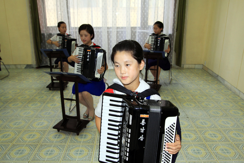 Young North Korean students playing accordions in the Mangyongdae Children's Palace.