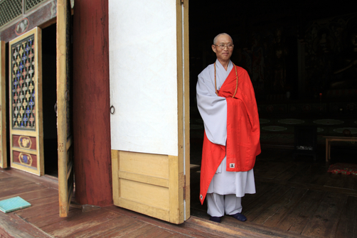 A Buddhist monk stands in the doorway of a temple in North Korea.