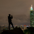 A man takes a picture with his phone of Taipei 101 Tower at night.