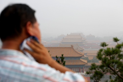 A man wipes sweat from his neck as air pollution hangs over the Forbidden City.
