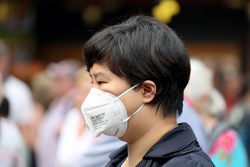 A woman wearing a mask to protect herself from air pollution.