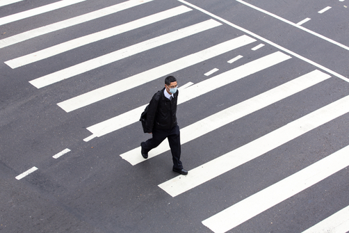 A man wearing a mask crosses a pedestrian crossing in Taipei.