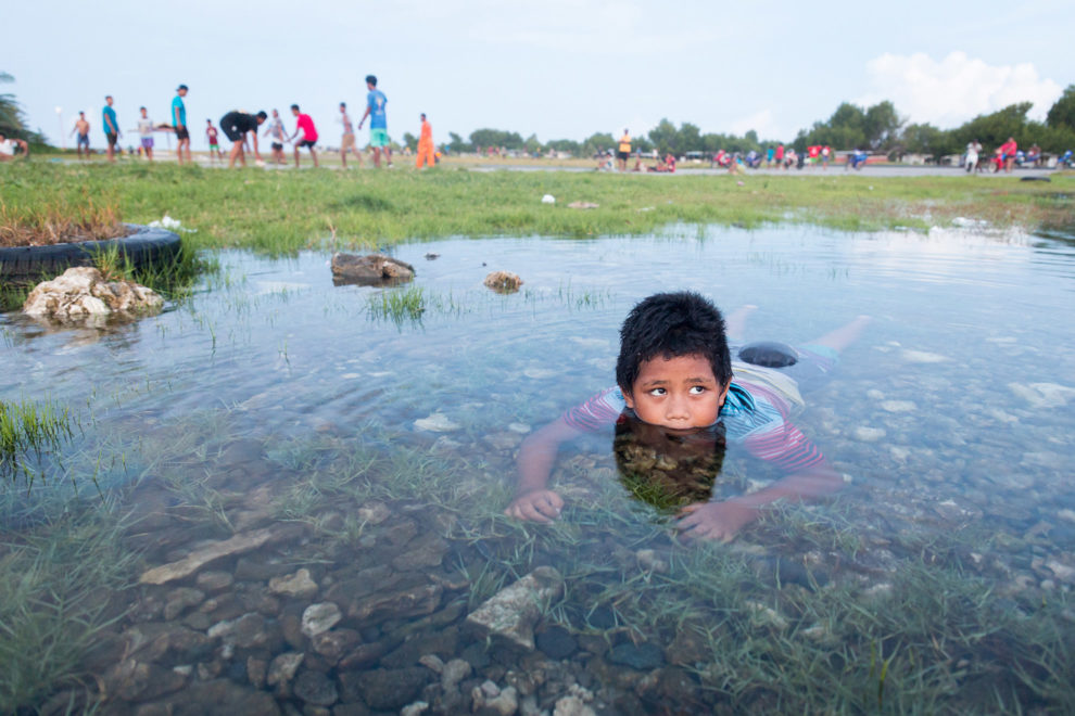 A young boy swims in a flooded area near the airport runway, in downtown Funafuti.
