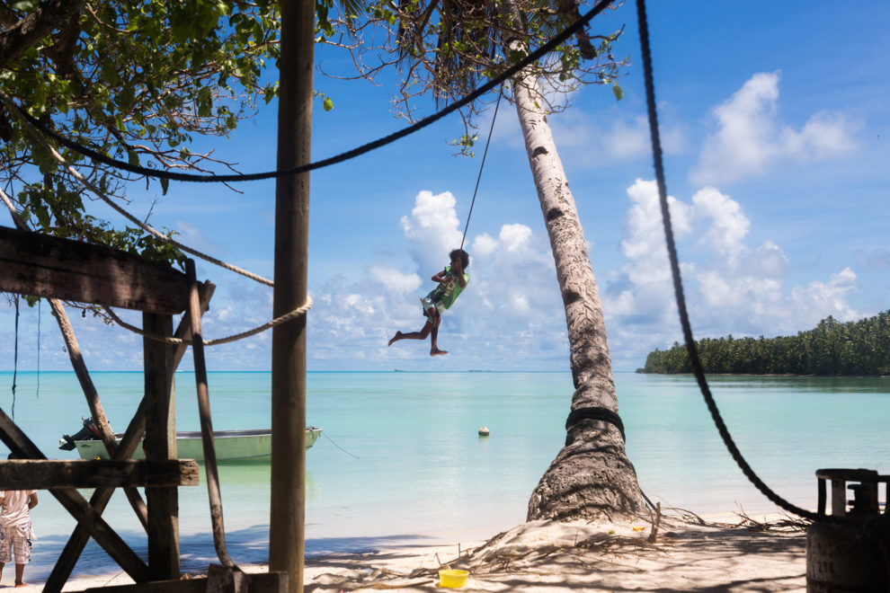A young boy swings from a tree on one of the islands in the Funafuti atoll.