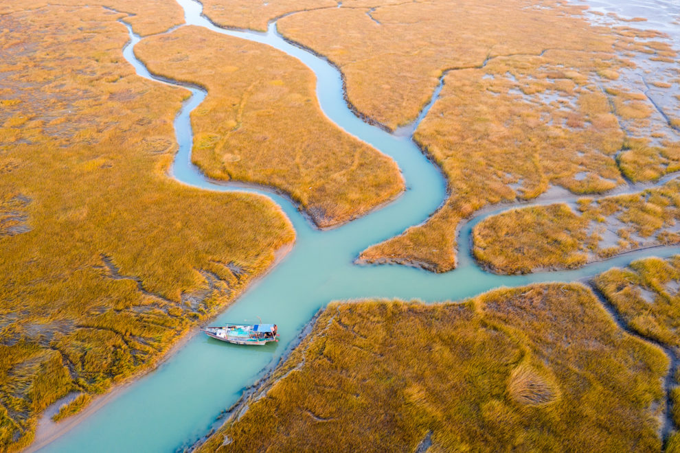 A fishing boat lies in a colourful small river that has formed in the lower reaches of the Yellow River estuary which marks the southernmost boundary of Bohai Bay. Shandong province, China. 2019