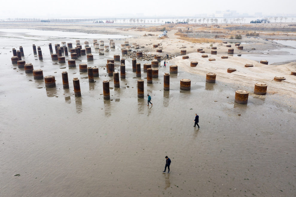 People search for shells by the remains of an unidentified structure, near the megacity of Tianjin in north-east China. Major infrastructure that supports the daily functioning of the city is often the first impacted as storm surges hit and sea levels rise. The city also has problems with land subsidence which exacerbates the problems faced. 2019