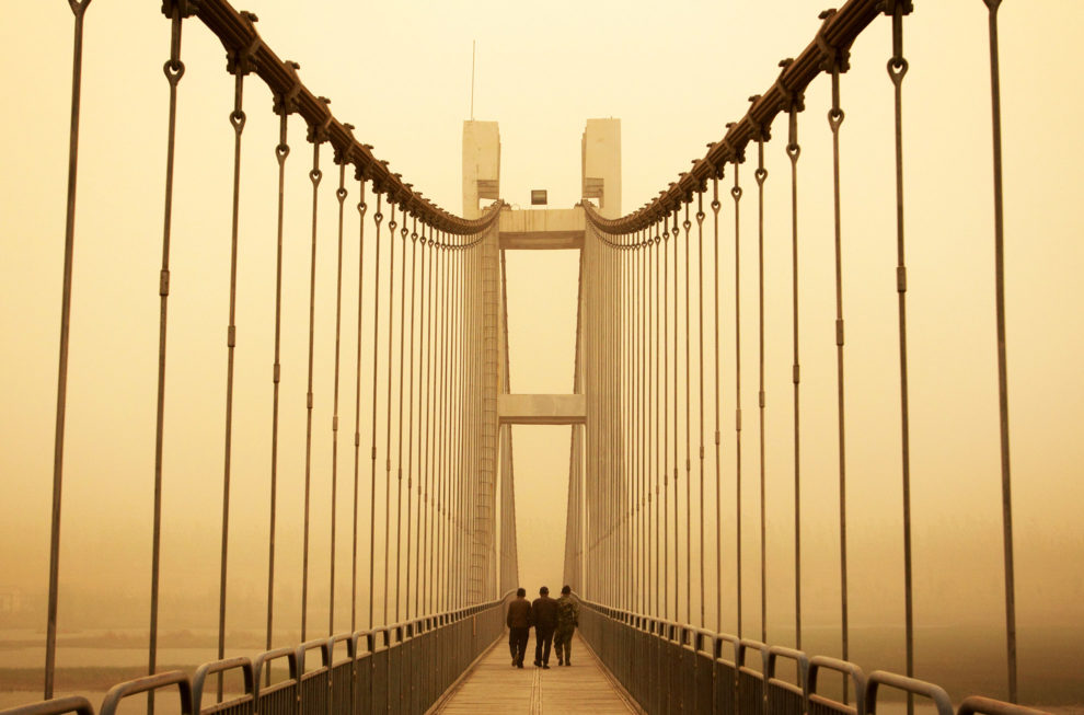 Three men cross a suspension bridge as it is engulfed in a large sandstorm that has descended upon Gansu Province, in western China.