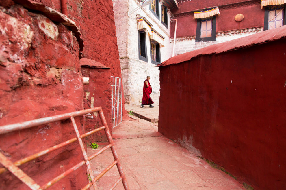 A monk walks through the narrow painted alleyways of Ganden monastery in Tibet. The holy monastery is one of the most important in the region and sits on top of a remote mountain near Lhasa at an altitude over approximately 4,300m.